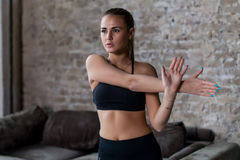 Jovem mulher apta no sportswear que fazem o ombro e no braço que estica o exercício antes do exercício dentro no apartamento do s fotos de stock royalty free