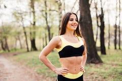 Jovem mulher apta no sportswear que prepara-se para o exercício Mulher saudável no parque em um dia ensolarado Fotografia de Stock