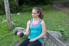 Jovem mulher apta que dá certo com um peso Fotografia de Stock Royalty Free