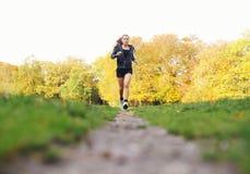 Jovem mulher apta que movimenta-se em um parque em um dia de verão Fotografia de Stock Royalty Free