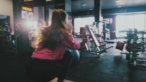 Jovem mulher apta que salta no pneu em um gym do estilo do crossfit O atleta fêmea está executando saltos video estoque