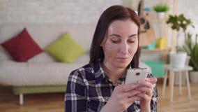 Jovem mulher ascendente próxima com uma cicatriz da queimadura em sua cara usando um smartphone filme