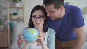 Jovem mulher ascendente próxima e um olhar do homem novo no globo filme