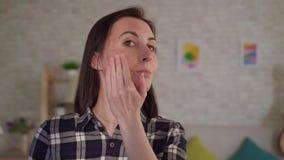 A jovem mulher ascendente próxima põe o creme sobre uma cicatriz de uma queimadura em sua cara filme