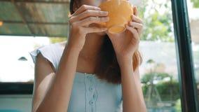 Jovem mulher asiática alegre que bebe o café ou o chá morno que apreciam o ao sentar-se no café filme