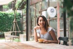 Jovem mulher asiática alegre que bebe o café ou o chá morno que apreciam o ao sentar-se no café imagens de stock royalty free