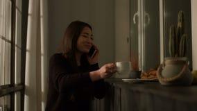 Jovem mulher asiática alegre que conversa no telefone celular vídeos de arquivo