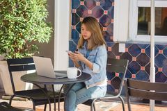 Jovem mulher asiática alegre que senta-se no café bebendo do café e que usa o smartphone para a fala, a leitura e texting fotos de stock