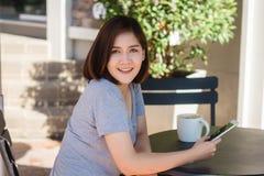 Jovem mulher asiática alegre que senta-se no café bebendo do café e que usa o smartphone para a fala, a leitura e texting imagem de stock royalty free