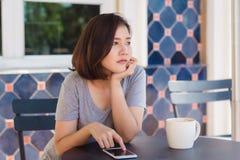 Jovem mulher asiática alegre que senta-se no café bebendo do café e que usa o smartphone para a fala, a leitura e texting foto de stock