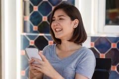 Jovem mulher asiática alegre que senta-se no café usando o smartphone para a fala, a leitura e texting fotos de stock royalty free