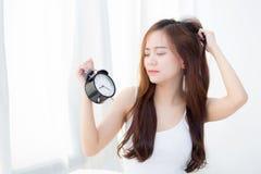 A jovem mulher asiática bonita acorda no despertador irritado manhã que guarda a mão foto de stock