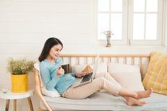 Jovem mulher asiática bonita ocasional feliz que trabalha em um portátil em Fotos de Stock
