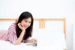A jovem mulher asiática bonita que encontra-se na cama usando o portátil no quarto para o lazer e relaxa fotografia de stock royalty free