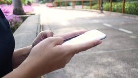 Jovem mulher asiática bonita que senta-se no banco no parque usando o smartphone para a fala, a leitura e texting vídeos de arquivo
