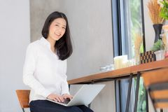 Jovem mulher asiática bonita que trabalha em linha no portátil Imagem de Stock Royalty Free