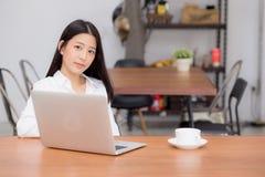 Jovem mulher asiática bonita que trabalha em linha no portátil que senta-se na cafetaria foto de stock royalty free