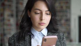 Jovem mulher asiática com o telefone que texting no fundo das estantes vídeos de arquivo