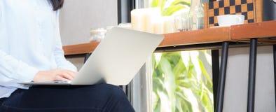 Jovem mulher asiática do Web site da bandeira do close up que trabalha em linha no portátil que senta-se na cafetaria foto de stock
