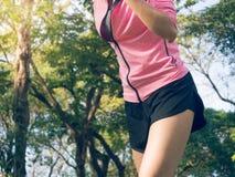 Jovem mulher asiática na marca a ajustar-se pronto para o exercício movimentando-se ao buld acima de seu corpo no vidro na manhã  foto de stock royalty free
