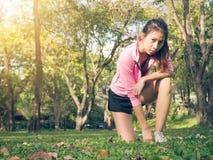 Jovem mulher asiática na marca a ajustar-se pronto para o exercício movimentando-se ao buld acima de seu corpo no vidro na manhã  imagem de stock