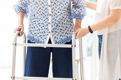 Jovem mulher asiática que ajuda a mulher superior em usar o caminhante durante a reabilitação, fim acima da equipe de tratamento  imagens de stock royalty free