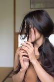 A jovem mulher asiática senta-se na sala do estilo de japão Fotografia de Stock