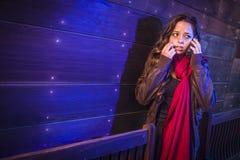 Jovem mulher assustado na passagem escura usando o telefone celular Imagens de Stock