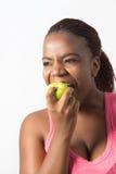 Jovem mulher ativa que morde uma maçã verde Foto de Stock Royalty Free