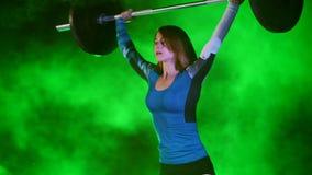 A jovem mulher atlética, aumentos o barbell, faz sentar-UPS com o barbell, ele o ` s duramente para ela Na noite, à luz de filme