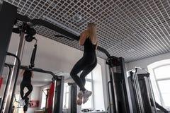 A jovem mulher atlética com um corpo bonito na roupa preta nas sapatilhas pendura em um simulador moderno na classe do esporte foto de stock royalty free