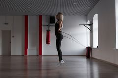 Jovem mulher atlética em saltos pretos do sportswear em uma corda de salto e em calorias das queimaduras em um estúdio da aptidão fotos de stock