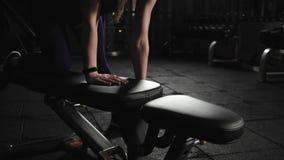 A jovem mulher atlética no gym levanta pesos do metal Exercício com peso no banco, nivelando o treinamento Fim acima vídeos de arquivo