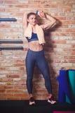 Jovem mulher atlética no sportswear que descansa de um exercício no fundo de uma parede de tijolo fotos de stock