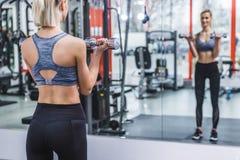 jovem mulher atlética que dá certo com pesos na frente do espelho imagens de stock royalty free