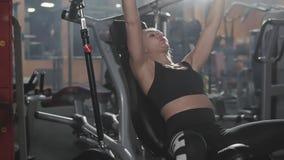 Jovem mulher atlética que dá certo no equipamento do exercício da aptidão no gym video estoque