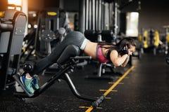 Jovem mulher atlética que faz a hiperextensão no gym Mulher que dobram para trás e músculos abdominais no banco imagem de stock royalty free