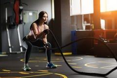 A jovem mulher atlética que faz o crossfit exercita com uma corda imagem de stock