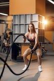 A jovem mulher atlética que faz o crossfit exercita com uma corda fotografia de stock royalty free