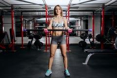 Jovem mulher atlética que faz o exercício pesado para o bíceps com peso da barra da aptidão no gym imagens de stock royalty free