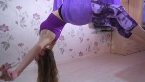 Jovem mulher atlética que faz o exersice da ioga com a rede na casa video estoque