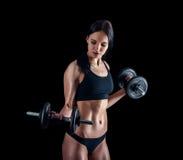 Jovem mulher atlética que faz um exercício da aptidão contra o fundo preto A menina atrativa da aptidão que bombeia acima muscles foto de stock