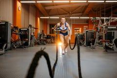 A jovem mulher atl?tica que faz o crossfit exercita com uma corda fotos de stock royalty free
