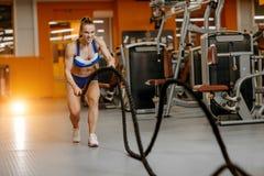 A jovem mulher atl?tica que faz o crossfit exercita com uma corda imagens de stock