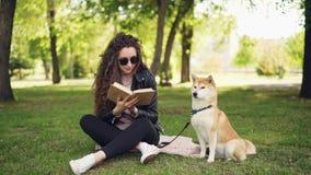 A jovem mulher atrativa é livro de leitura que senta-se na grama no parque quando seu cão bem-produzido se sentar perto de seu pr filme