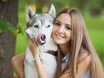 A jovem mulher atrativa abraça o cão engraçado do cão de puxar trenós siberian Fotografia de Stock
