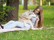 A jovem mulher atrativa abraça o cão engraçado do cão de puxar trenós siberian e dá h Fotos de Stock