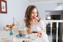 A jovem mulher atrativa alegre que senta e que come o coração deu forma a cookies Imagens de Stock