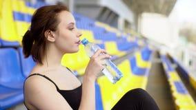 A jovem mulher atrativa bebe a água em uma tribuna video estoque