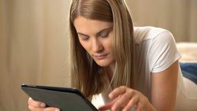 Jovem mulher atrativa bonita em um t-shirt branco com um tablet pc que encontra-se em um sofá Internet da consultação e video estoque